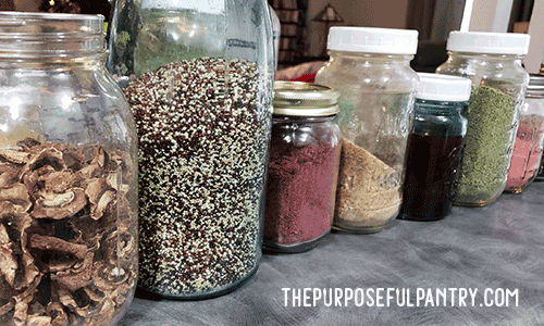 Canning jars in a row full of food storage items from the pantry. 13+ ways to re-purpose canning jars for the home.
