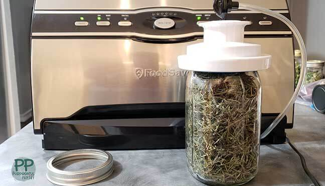 Food Saver vacuum sealer sealing a jar of dried rosemary and canning jar ring next to it