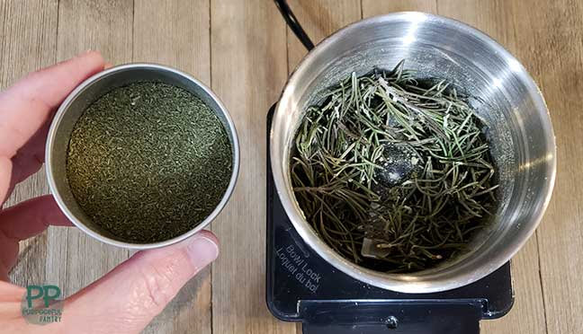 Dried rosemary in a coffee grinder next to a container full of ground rosemary.