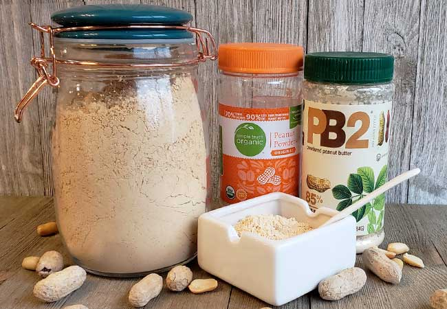 Glass jar full of peanut butter powder and dish with powder on wooden background with peanuts strewn around