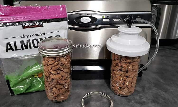 2 mason jars of almonds with a Food Saver for storing nuts