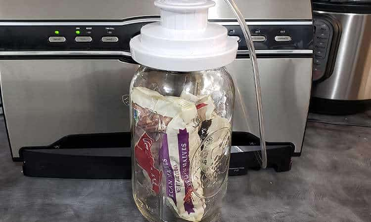 large mason jar full of packaged nuts in front of FoodSaver vacuum sealer for storing nuts