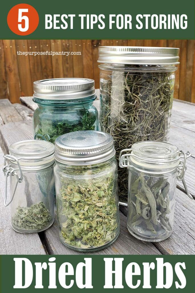 Mason jars for storing dried herbs on a picnic table in front of a rust colored fence.
