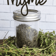 Mason jar of dried time on a bed of fresh thyme for How to Dehydrate Thyme