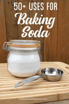 Jar of baking soda on a cutting board wit a measuring spoon with text 50 ways to use baking soda