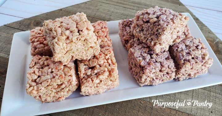 Strawberry and blueberry rice krispie treats on a white tray setting on a wooden background