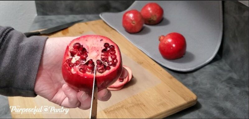 Red pomegranate over cutting board showing natural segments