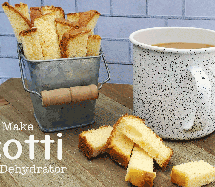 DIY Biscotti in a metal container with white coffee cup on wooden background.