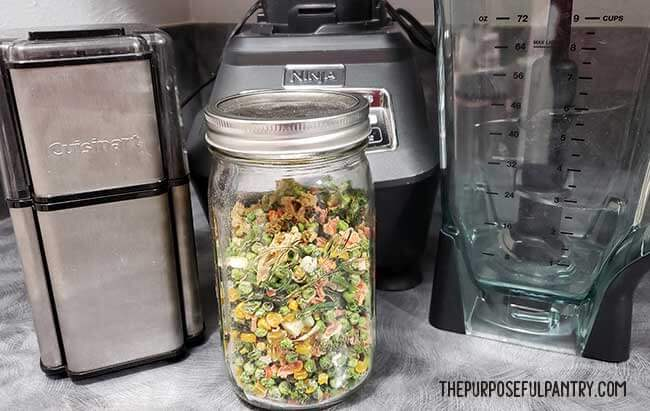 Jar of finished dehydrated mixed vegetables in front of grinder and blender