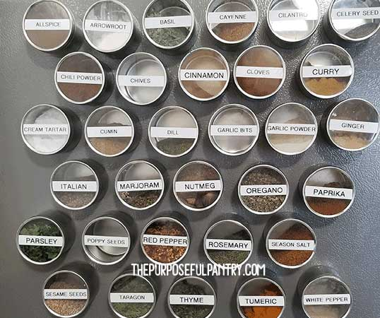 Magnetic spice canisters on the side of a gray referigerator