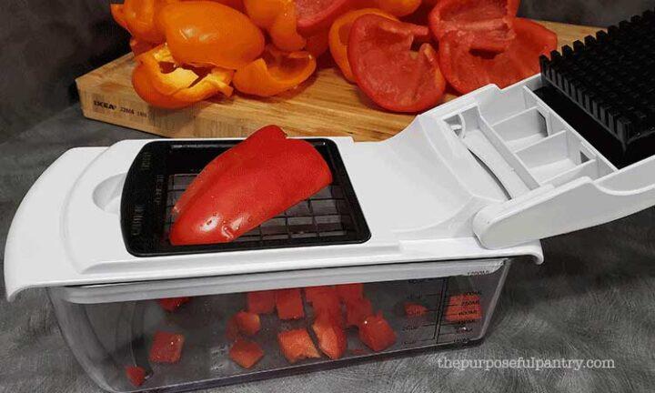 Red bell pepper being diced in a Fullstar Vegetable Chopper