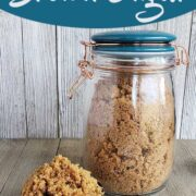 A jar of homemade brown sugar with a measuring cup of brown sugar heaped inside on a wooden surface
