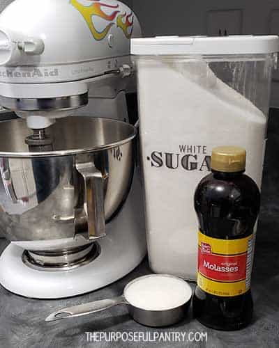 Kitchen Aid mixer, a container of white sugar, and a bottle of molasses for homemade brown sugar