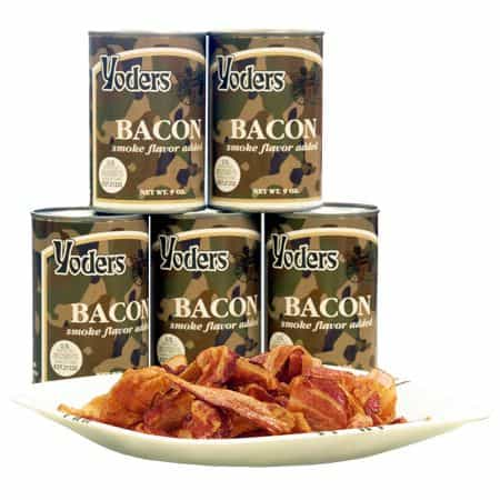 Cans of Yoders canned bacon in a stack with a dish of the bacon in front of them.