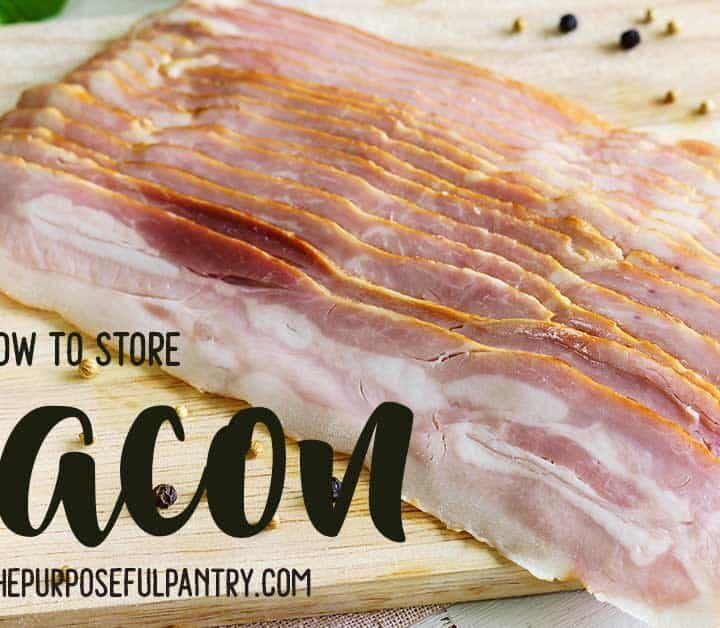 slab of bacon on a wooden cutting board surrounded by herbs and spices