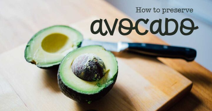 Fresh avocado that is halved with a knife on a wooden cutting surface