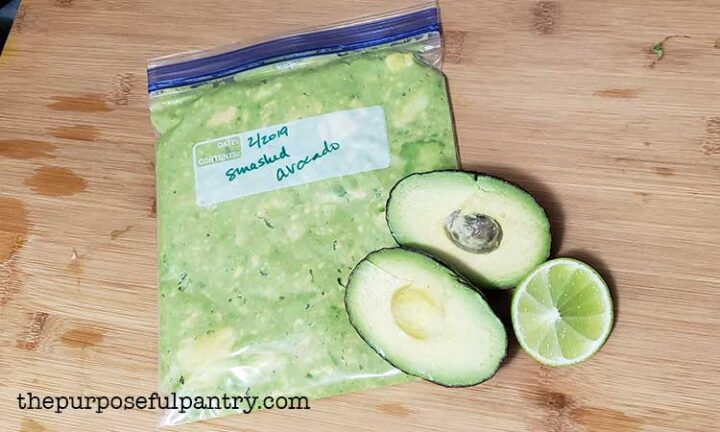 fresh avocado halved, with lime, and a bag of smashed avocado for the freezer