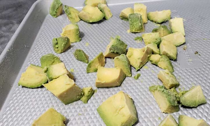 chunks of avocado on a stainless steel cookie sheet being prepared to be flash frozen