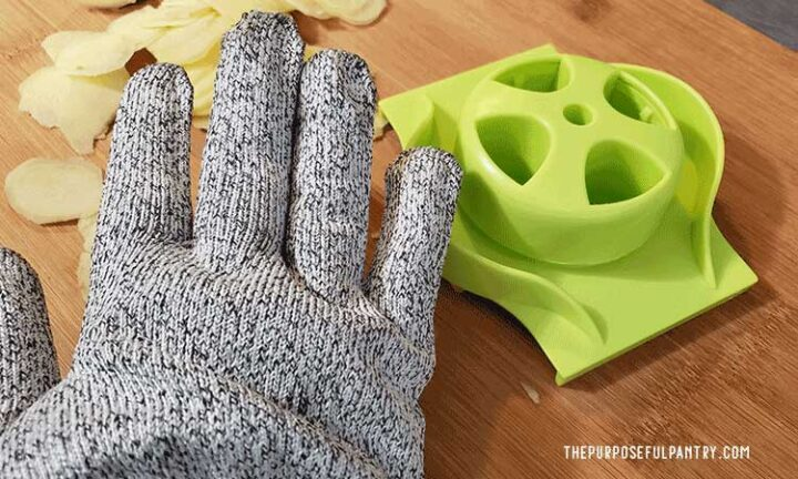 Gray cutting glove, with green guard from a mandoline and ginger slices