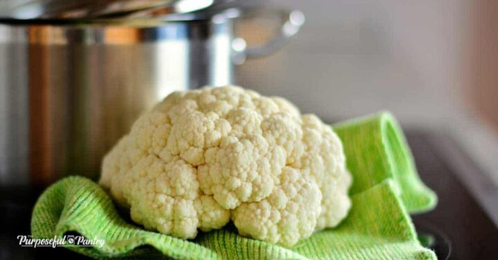 cauliflower on a green cloth in front of a stockpot