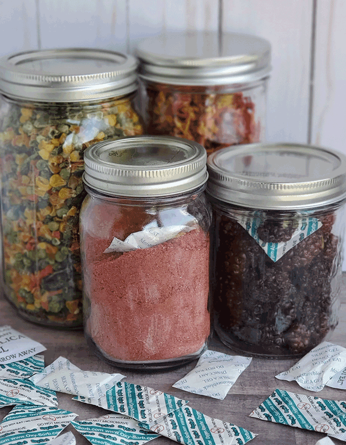 4 canning jars full of dehydrated foods and powders, on a wooden background surrounded by deisccant packs and o2 absorbers