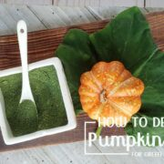 Pumpkin leaf and green pumpkin powder on a wooden surface with small pumpkin and serving dish