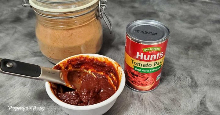 Tomato paste in a white dish with jar of tomato powder and can of tomato paste