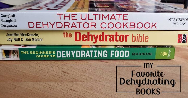A stack of Dehydrating cookbooks on a wooden table