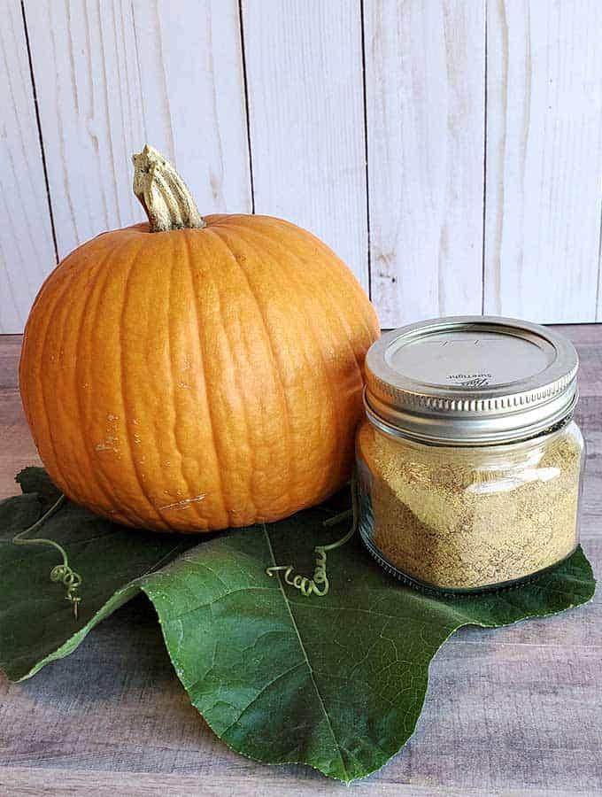 Pumpkin and a jar of dehydrated pumpkin powder in a jar on a pumpkin leave on a wooden surface