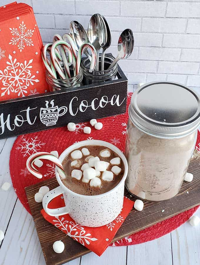 Hot cocoa mix in a jar with a cup of hot cocoa and decorated table.