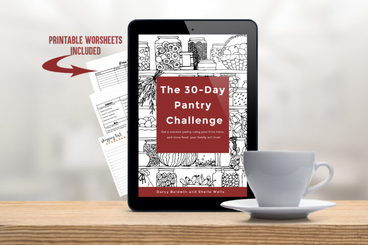 Tablet with the cover of the 30 Day Pantry challenge on a table with a white coffee cup.
