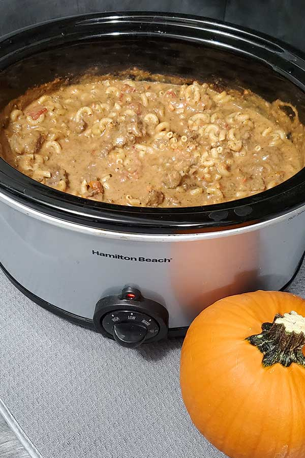 Slow cooker full of supper with a pumpkin next to it