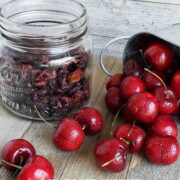 jar of dehydrated cherries alongside a silver serving dish of fresh cherries spilling onto a wooden surface