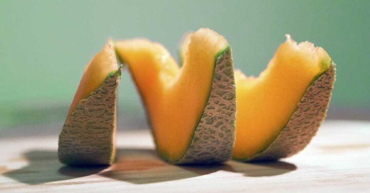 sliced muskmelon on a tabletop with blue background