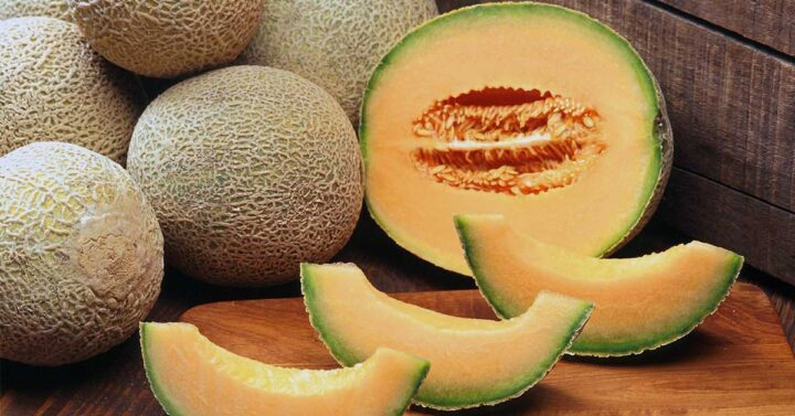 Whole, halved and sliced cantaloupes on wooden background.