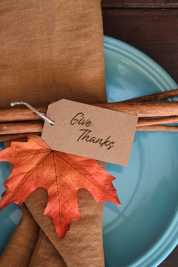 Fall decor on a blue plate with a tag that reads Give Thanks
