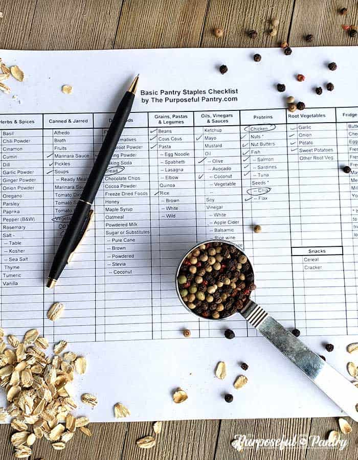 Pantry checklist on wooden surface with pen and various cooking ingredients scattered on it