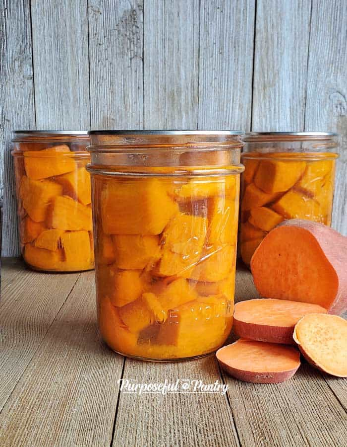 Mason jars of canned sweet potatoes with a fresh-cut up sweet potato all on a wooden backgroud