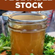 Canned jar of vegetable stock on a bed of fresh vegetables.