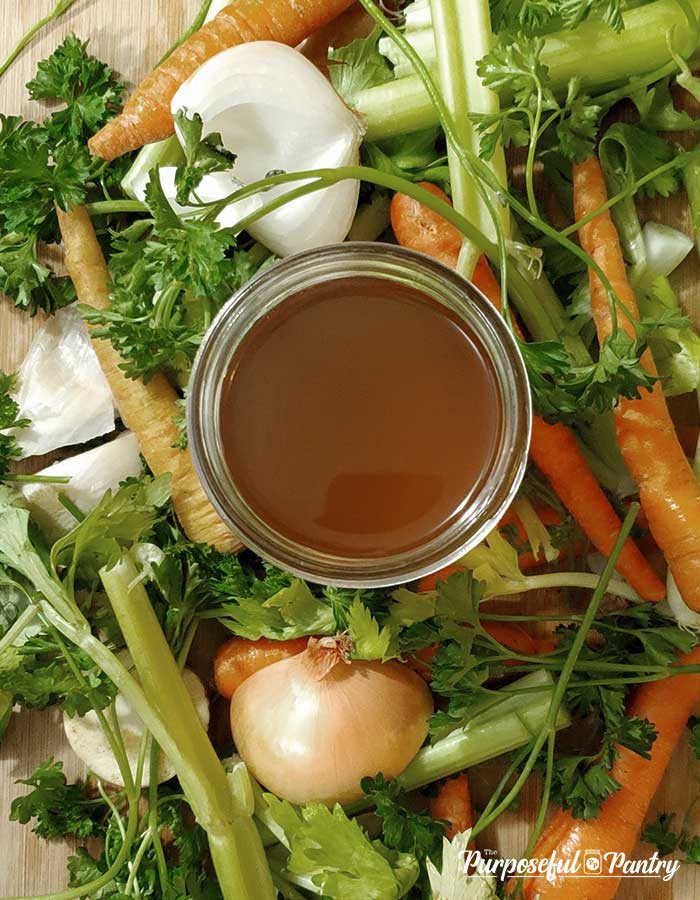 Top view of a jar of deep amber vegetable broth on a bed of fresh vegetables