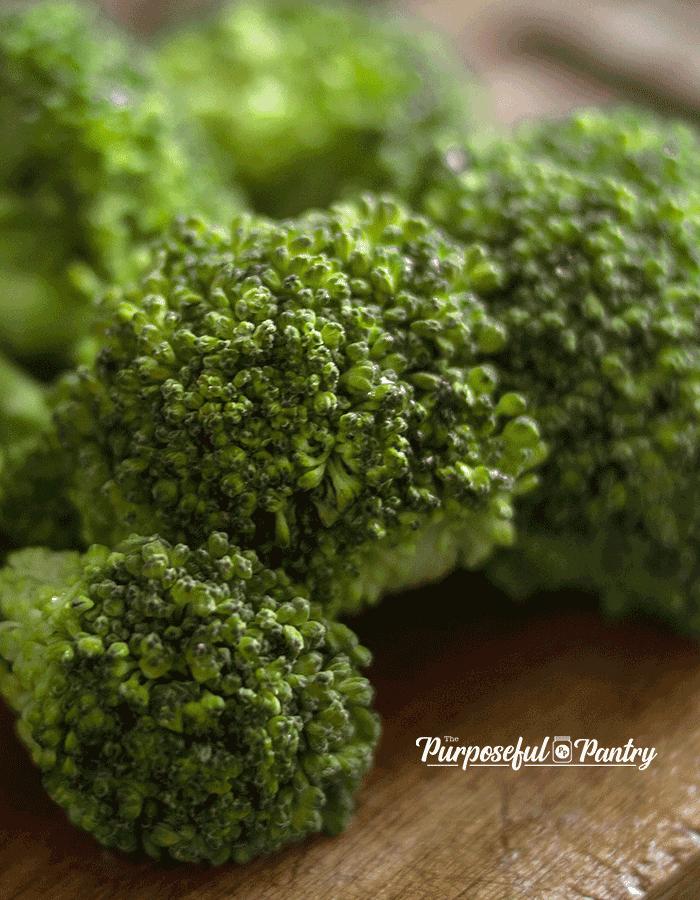 Broccoli florets on a wooden cutting board.