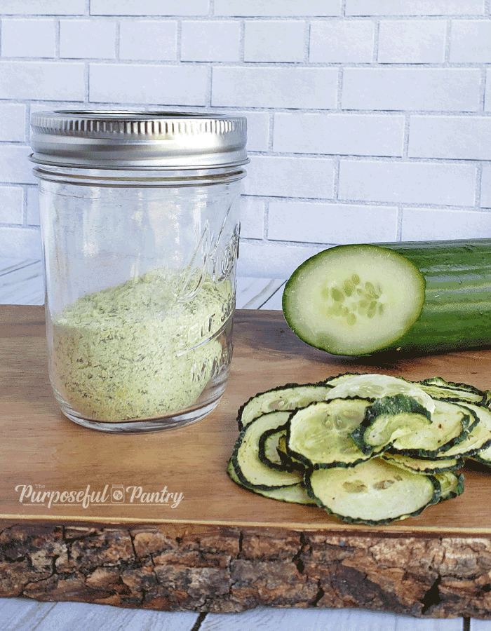 Jar of cucumber powder with a fresh English cucumber and dehydrated cucumber chips on wooden cutting board.