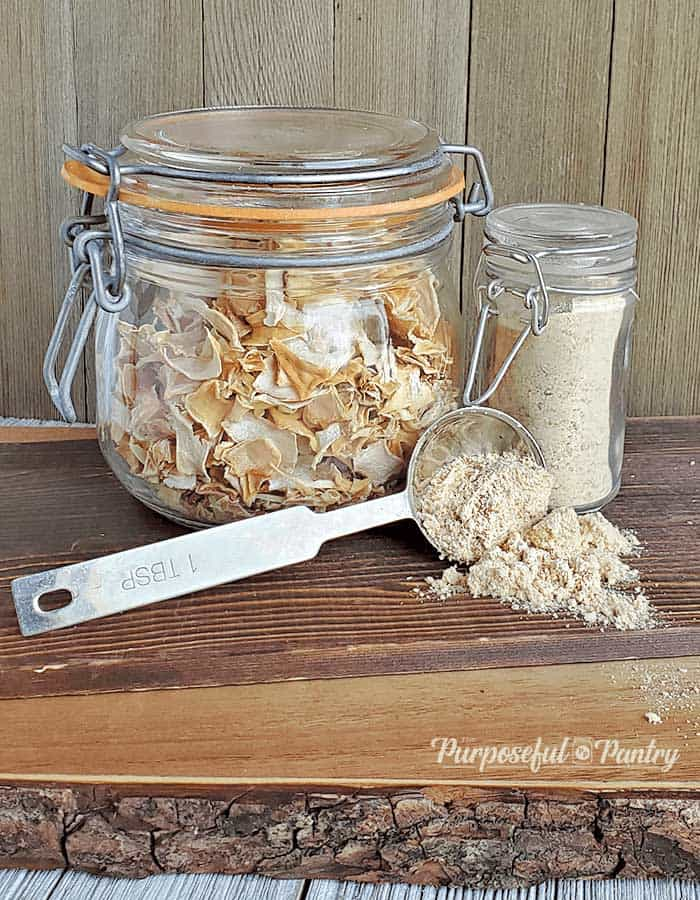 Clamp jar with dehydrated onions, a jar of dehydrated onion powder, and a measuring spoon of dehydrated onion powder spilling onto a wooden surface