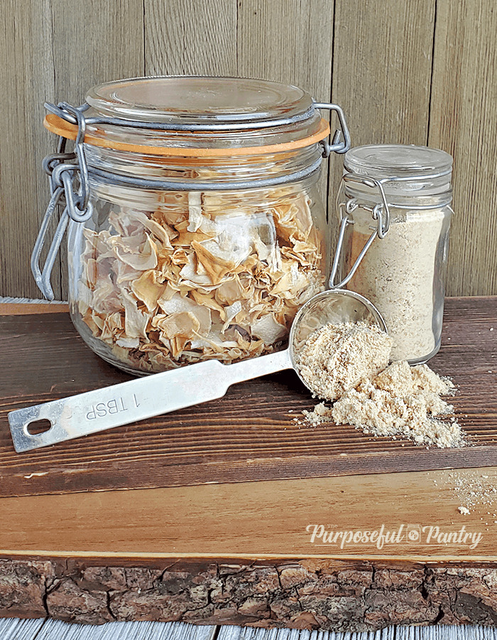 clamp jar of dried onion pieces with a jar of onion powder, and a spoon spilling onion powder onto wooden surface.
