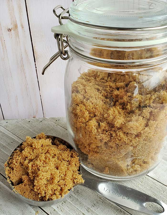 Pantry glass jar full of homemade brown sugar + measuring spoon showing finished brown sugar