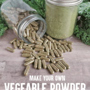 Bottle of vegetable powder capsules spilling in front of jar of dehydrated green powder in front of fresh greens for Pin