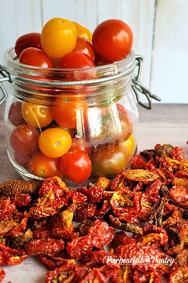 Glass jar of cherry tomatoes with dried tomatoes scattered around it
