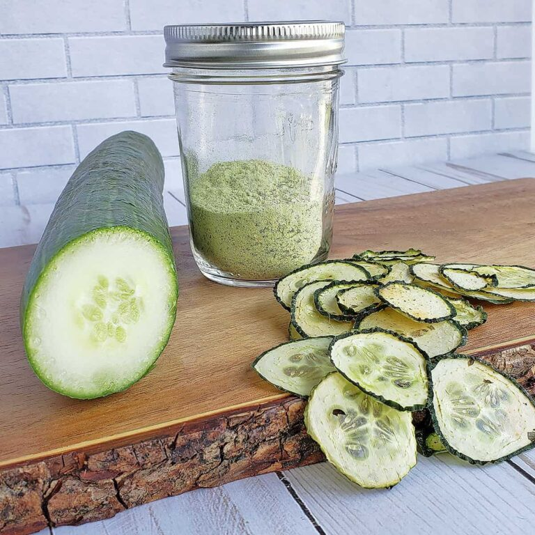 English cucumber sliced, a jar of cucumber powder, and dehydrated cucumbers on a wooden serving tray