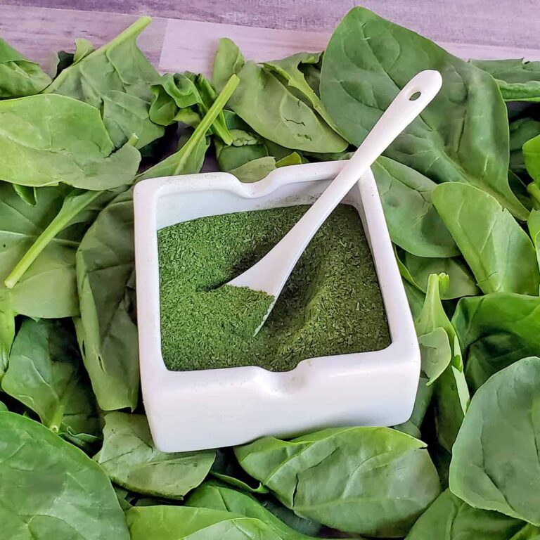 Fresh spinach as a bed or a white dish full of spinach green powder