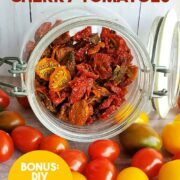 Glass jar of dehydrated tomatoes spilling onto table of fresh cherry and grape tomatoes